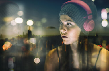 Portrait of young woman with headphones at twilight - UUF11626