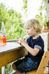 Little boy sitting at table on balcony drinking beverage - SPFF00018