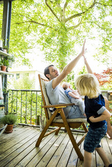 Father and little son high fiving on balcony - SPFF00021