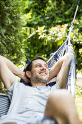Portrait of laughing mature man lying in hammock in the garden - SPFF00048