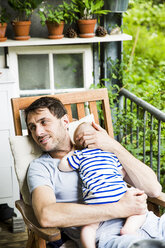 Portrait of smiling mature man with baby boy on his arms on balcony - SPFF00054