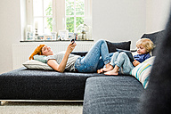 Mother and little son relaxing together on the couch with cell phone and tablet - SPFF00060