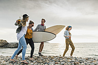 Happy friends with surfboards walking on stony beach - UUF11639