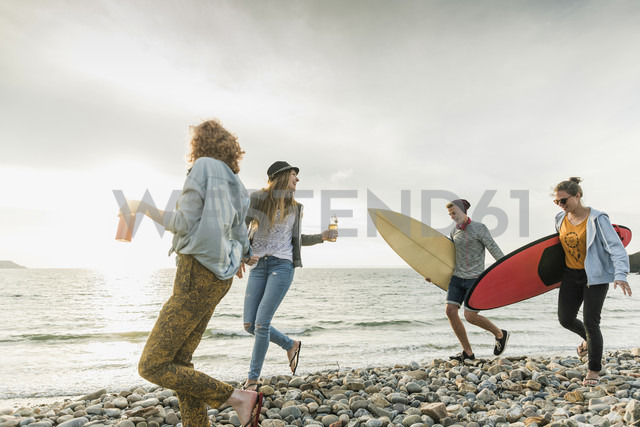 Happy friends with surfboards walking on stony beach - UUF11642