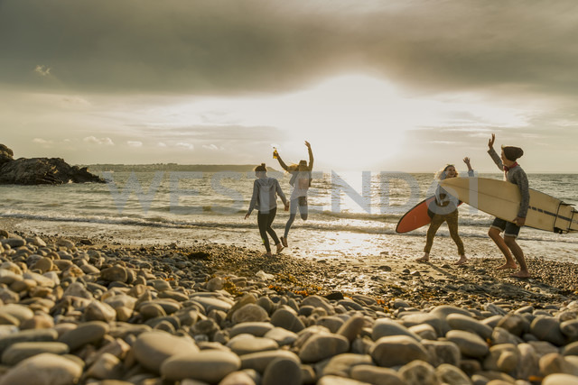 Excited friends with surfboards on stony beach - UUF11645