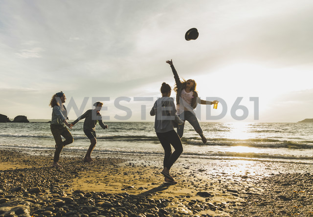 Excited friends on the beach at sunset - UUF11648