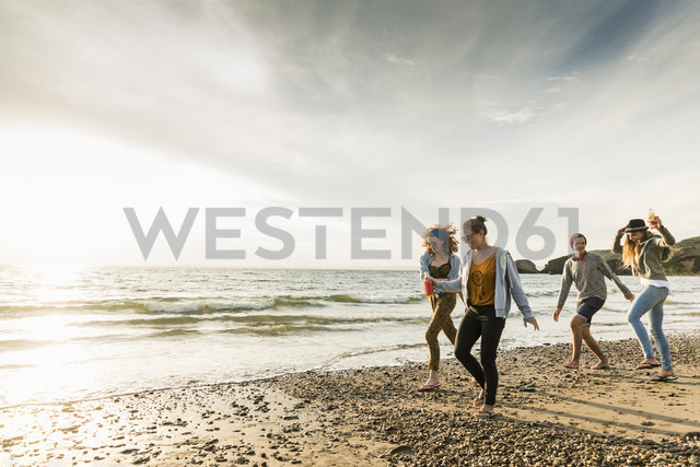 Happy friends walking on the beach at sunset - UUF11651