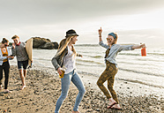 Happy friends with surfboard and drinks walking on stony beach - UUF11654