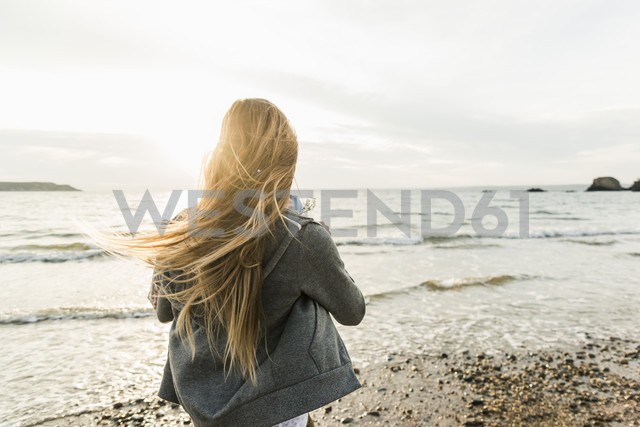 Young woman watching the sunset on the beach - UUF11657