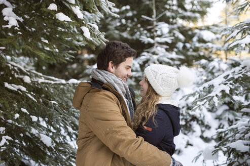 Happy young couple face to face in  snow-covered winter forest - HAPF02022
