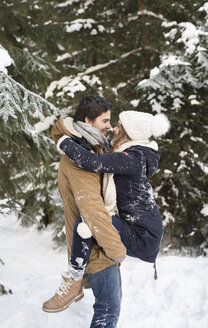 Happy young couple face to face in  snow-covered winter forest - HAPF02025