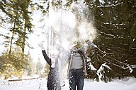 Happy young couple throwing snow in the air in the forest - HAPF02028