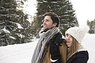 Happy young couple in  snow-covered winter forest - HAPF02034