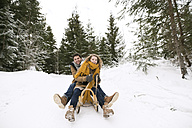 Happy young couple on sledge in winter forest - HAPF02043