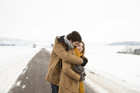 Young couple in love standing on country road in snow-covered landscape - HAPF02055
