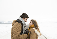 Young couple in love standing face to face on country road in snow-covered landscape - HAPF02058