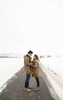 Young couple in love standing face to face on empty country road in snow-covered landscape - HAPF02061
