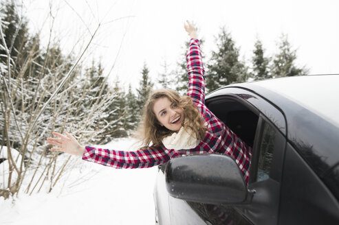 Portrait of laughing young woman leaning out of car window - HAPF02064