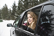 Young woman looking out of a car window in winter landscape - HAPF02067