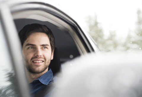 Portrait of smiling young man driving car in winter - HAPF02070