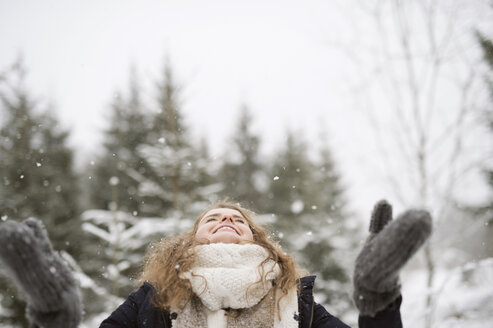 Happy young woman enjoying snowfall in winter forest - HAPF02073