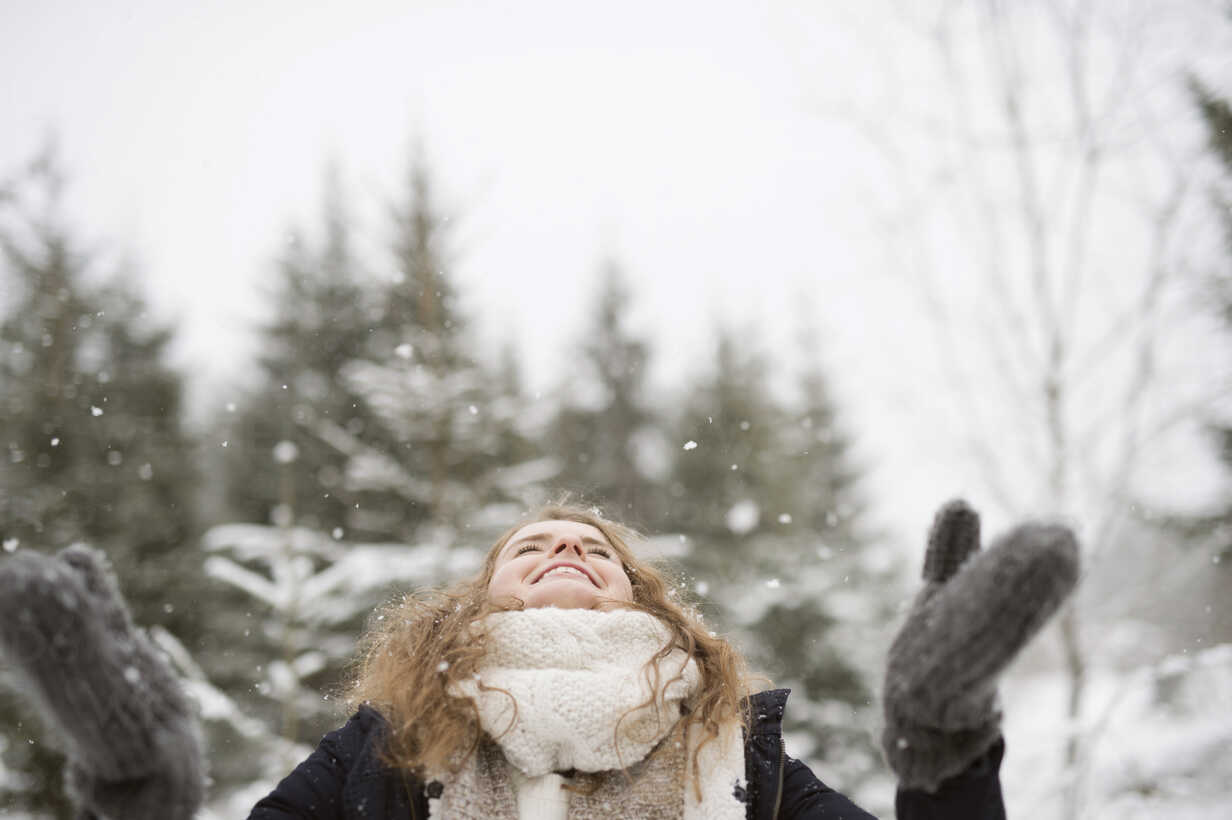 Happy young woman enjoying snowfall in winter forest - HAPF02073 - HalfPoint/Westend61