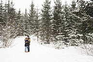 Happy young couple standing face to face in snow-covered winter forest - HAPF02076