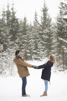 Happy young couple standing hand in hand in winter landscape - HAPF02082