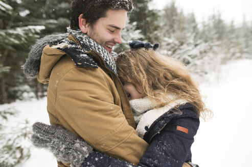 Happy young couple having fun in snow-covered winter forest - HAPF02085