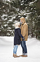 Happy young couple standing face to face in snow-covered winter landscape - HAPF02091