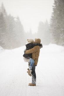 Happy young couple face to face in snow-covered winter landscape - HAPF02094