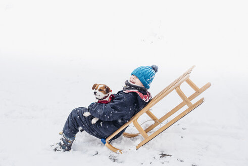 Little boy with his dog on a sledge in snow - MJF02164