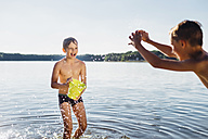 Two boys splashing with water at lakeshore - MJF02179
