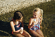 Two girls sitting in water at lakeshore eating icecream - MJF02185