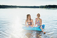Two girls sitting on swim toy in the water - MJF02191