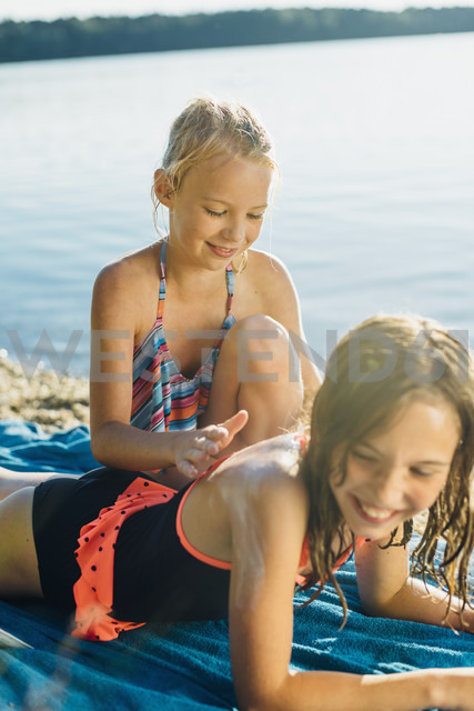 Girl applying sunscreen on shoulder of her friend on the beach - MJF02194