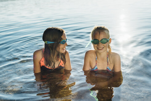 Two smiling friends with swimming goggles at lakeshore - MJF02197