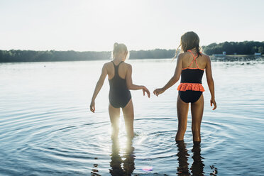 Back view of two friends wearing swimsuits standing at lakeshore - MJF02200