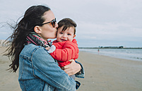 Portrait of smiling baby girl on her mother's arms on the beach - GEMF01775
