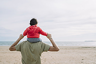 Back view of father carrying his little daughter on shoulders on the beach - GEMF01778