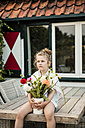 Girl holding bunch of flowers on terrace table - MOEF00062