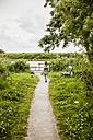 Girl walking on path towards lake - MOEF00065