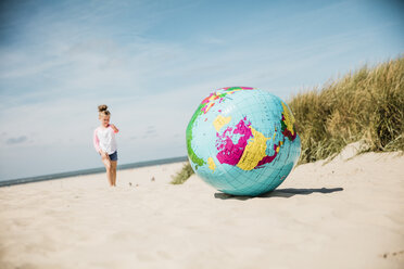 Globe on the beach with girl in background - MOEF00074
