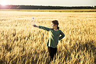 Girl standing in grain field holding miniature wind turbine - MOEF00092