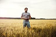 Man standing in grain field holding miniature wind turbine - MOEF00101