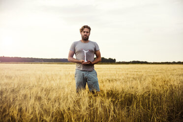 Man standing in grain field holding miniature wind turbine - MOEF00101