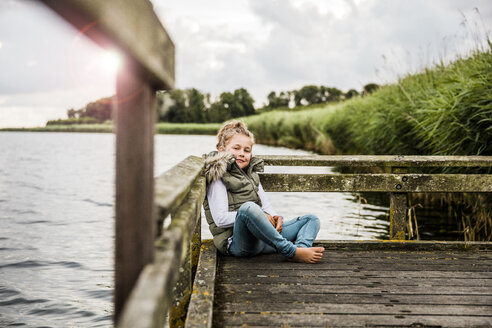 Girl sitting on jetty at a lake - MOEF00104
