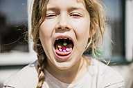 Girl with sweets in her mouth - MOEF00113