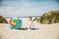Girl with globe on the beach - MOEF00125