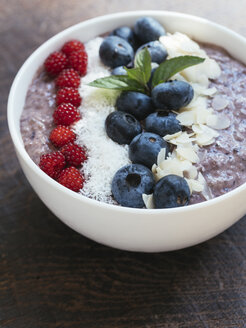 Bowl of blueberry smoothie with chia, coconut flakes, almonds and Japanese Wineberries - HAWF00966